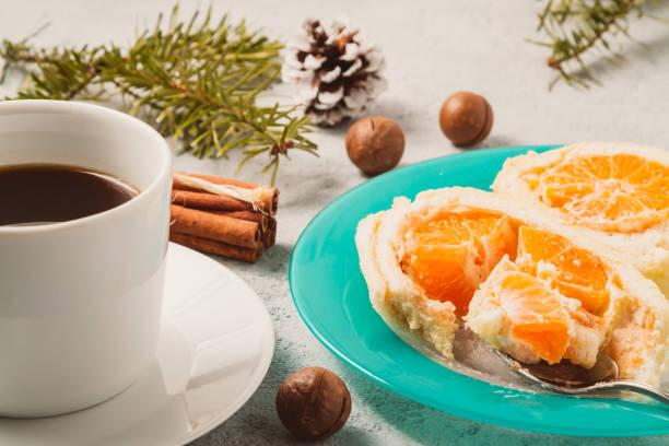 Süße Rolle mit Schlagsahne und Mandarinenfüllung und Weihnachtsdekoration enden und eine Tasse Kaffee – Foto