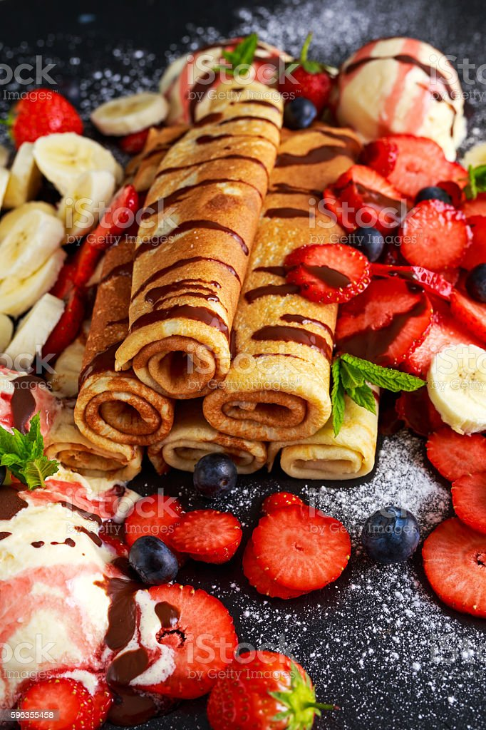 Sweet Rolled Pancakes with nutella, strawberry, blueberry, banana, ice cream. royalty-free stock photo
