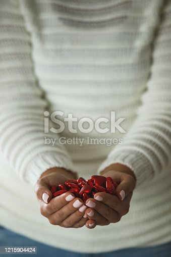 Mid section of woman holding bunch of red heart-shaped chocolates and offering them during Valentine's day.