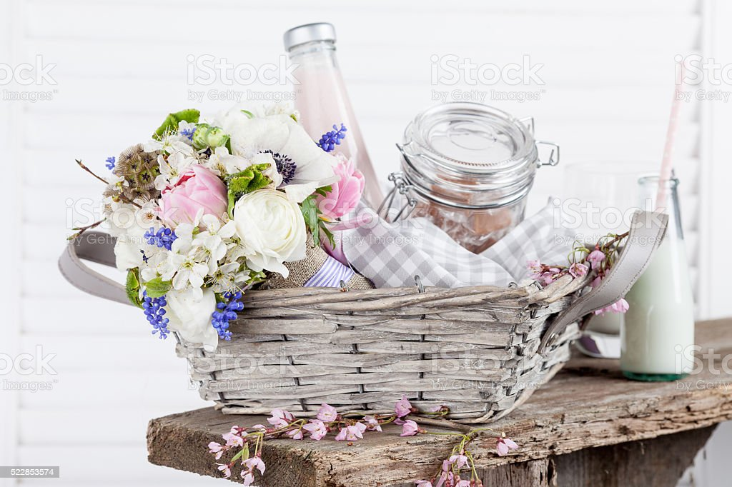 Sweet, rustic picnic basket with milk and flowers stock photo