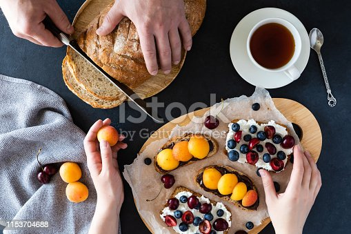 Sweet sandwiches with cream-cheese and fresh berries and fruit over a black background. Top view. healthy breakfast.