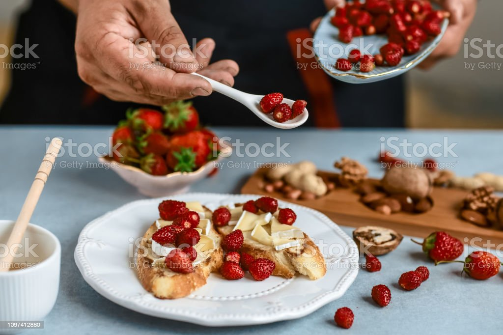 Sweet sandwiches with strawberries, cheese, camembert, brie, nuts and honey on the whole grain bread bruschetta cooking by chef hand on light background. Food recipe stock photo