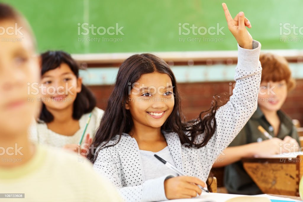 Sweet school girl raising her hand and smiling royalty-free stock photo