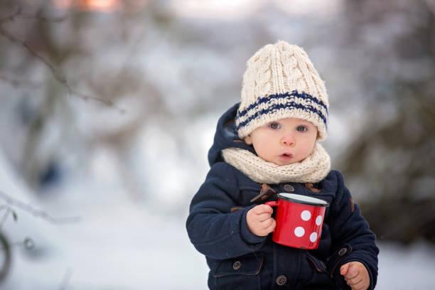 hermanos dulces, niños que tienen fiesta de invierno en el bosque nevado.  hermanos jóvenes, chicos, bebiendo té de termo. bebidas calientes y bebidas en clima frío - invierno fotografías e imágenes de stock