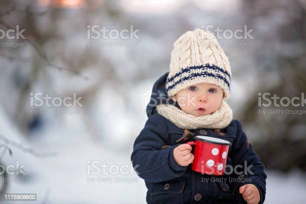 Photo of Sweet siblings, children having winter party in snowy forest.  Young brothers, boys, drinking tea from thermos. Hot drinks and beverage in cold weather