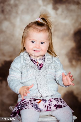 istock Sweet smiling little girl with blond hair sitting on chair 476128000