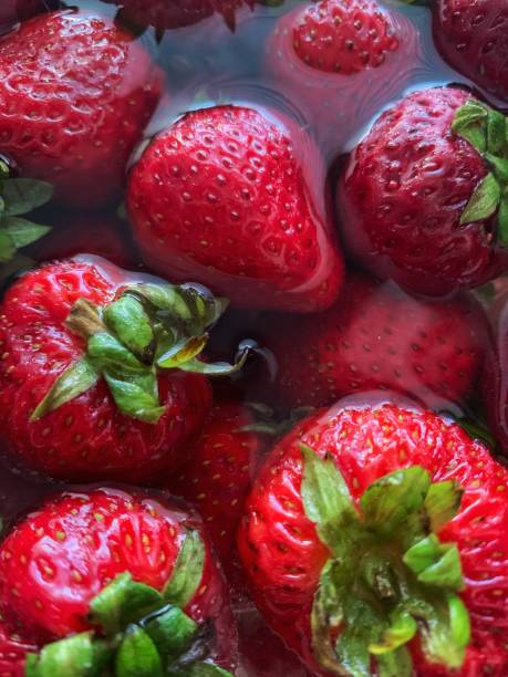 Sweet summer strawberries soaking and washing I. Water stock photo