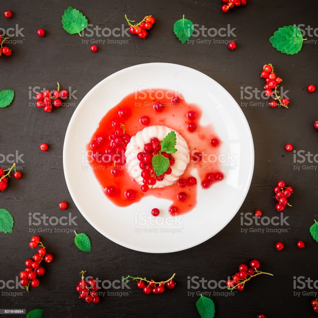 Sweet tasty jelly with berries in white plate on a dark table. Flat lay. Top view stock photo