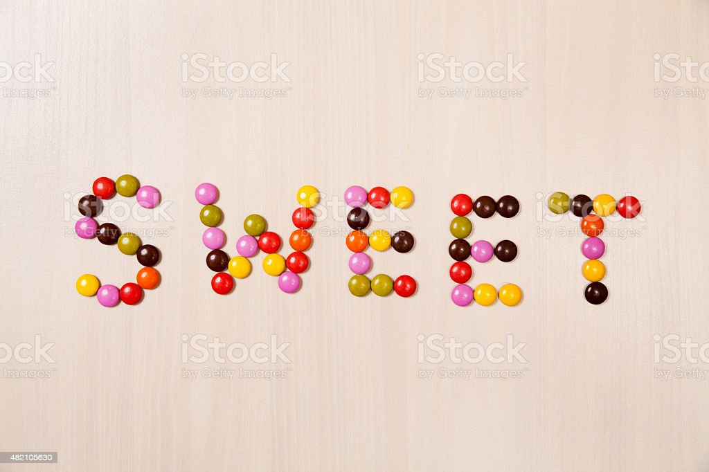 sweet text written with candy pills stock photo
