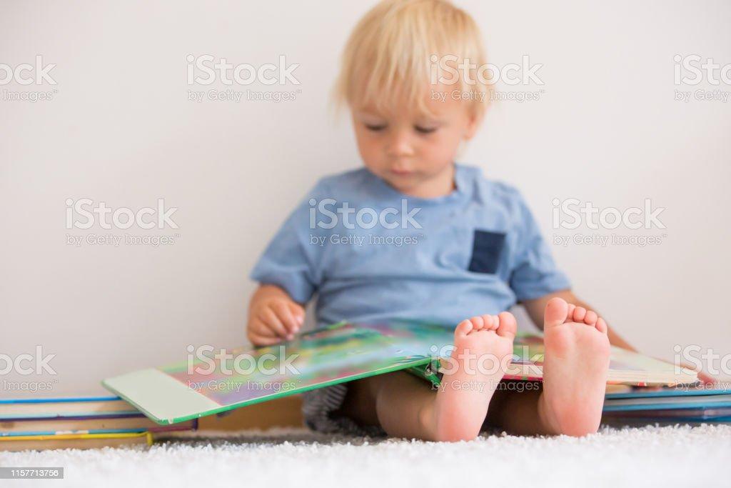 Dulce niño pequeño, libro de lectura en casa, sentado en el suelo, un montón de libros - Foto de stock de Alegre libre de derechos