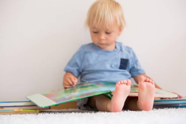 Dulce niño pequeño, libro de lectura en casa, sentado en el suelo, un montón de libros - foto de stock