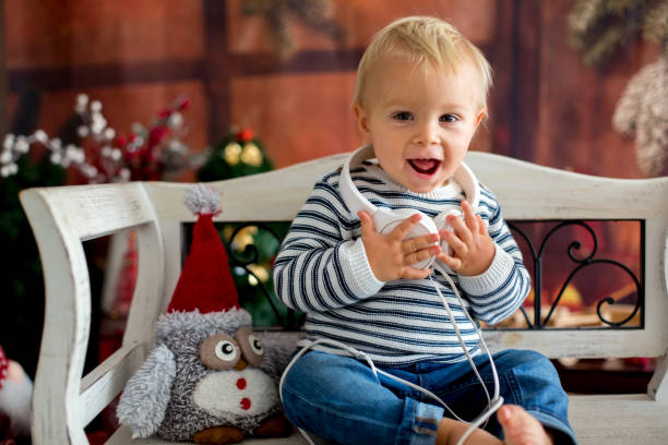 Niño niño dulce con auriculares, escuchando música, sentado sobre un banco rústico, decoración de Navidad detrás de él - foto de stock