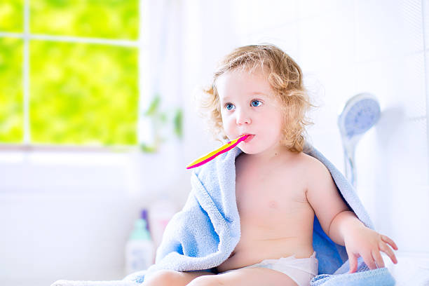 Sweet toddler girl brushing teeth stock photo