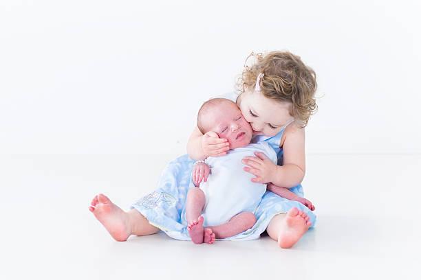 niedlichen kleinkind mädchen küssen ihr neugeborenes baby-bruder - taufe texte stock-fotos und bilder