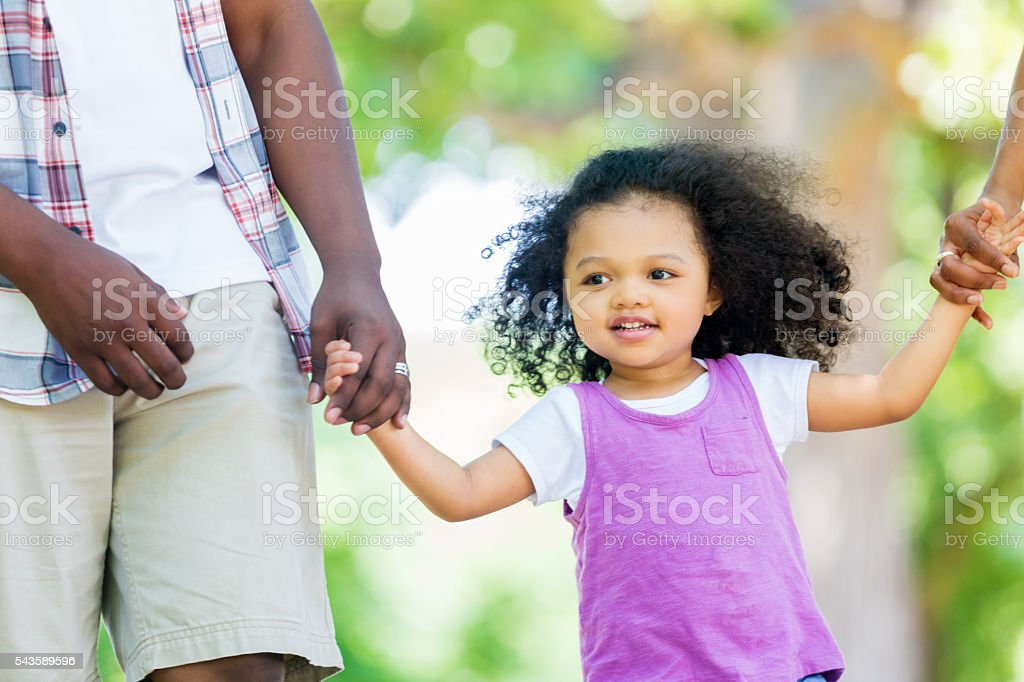 Sweet toddler takes a walk with parents in park stock photo