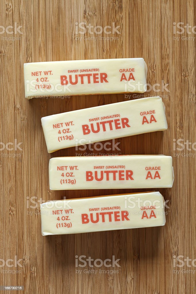 Sweet Unsalted Butter in Wrapper on Cutting Board stock photo