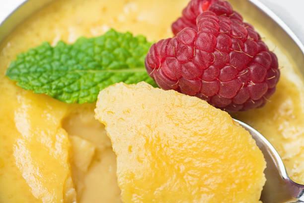 süße vanille eiercreme sahne torte mit frischen himbeeren und minze portion cup schöpfte mit einem teelöffel. makro-food-fotografie. sichtbare cremige textur und karamell-sirup. goldene zuckerkruste. - portugiesische desserts stock-fotos und bilder