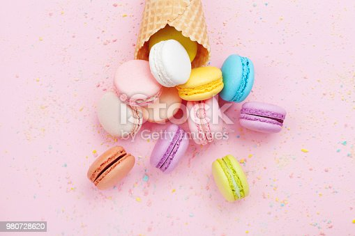 istock Sweet waffle cone with macaron or macaroon on pink pastel background top view. Flat lay. 980728620