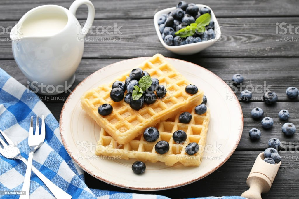 Sweet waffle with bluberries and jar of milk on black wooden table stock photo