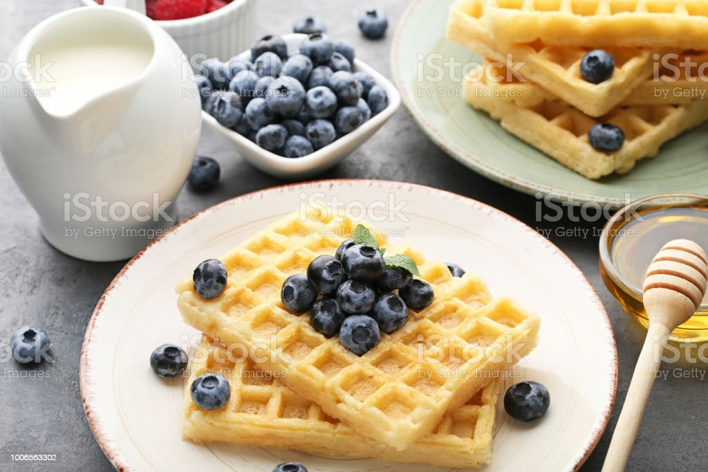 Sweet waffle with bluberries, milk and honey on grey wooden table stock photo