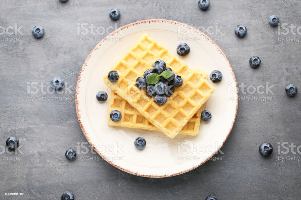 Sweet waffle with bluberries on grey wooden table stock photo