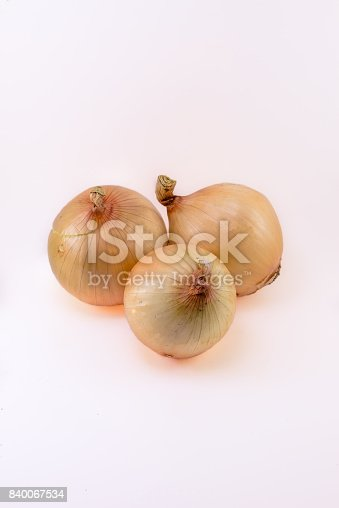 Sweet yellow onions isolated on white background in portrait orientation. This kind of vegetable is so common in every kitchen because of its sweet flavor as spice, or could be eaten raw in salads. It also has several health benefits as a natural cure for many diseases, and helps detoxify the body and boost the immune system.