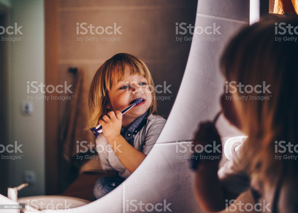 sweet young boy is brushing teeth stock photo