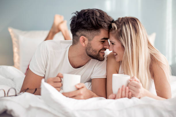 Sweet young couple lying in bedroom Young beautiful couple drinking coffee in bed at morning. couple in bed stock pictures, royalty-free photos & images