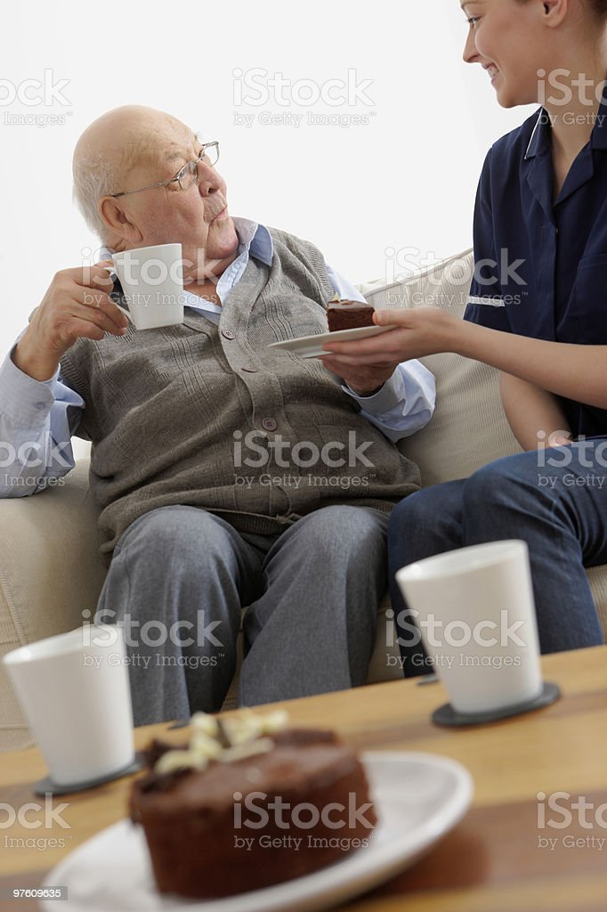 Sweet young girl giving chocolate cake to old man royalty-free stock photo