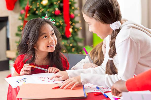 sweet young girls creating christmas cards together - winterdeko basteln stock-fotos und bilder