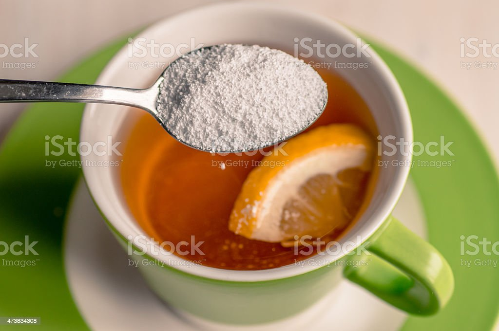 Sweetener in a cup of tea stock photo