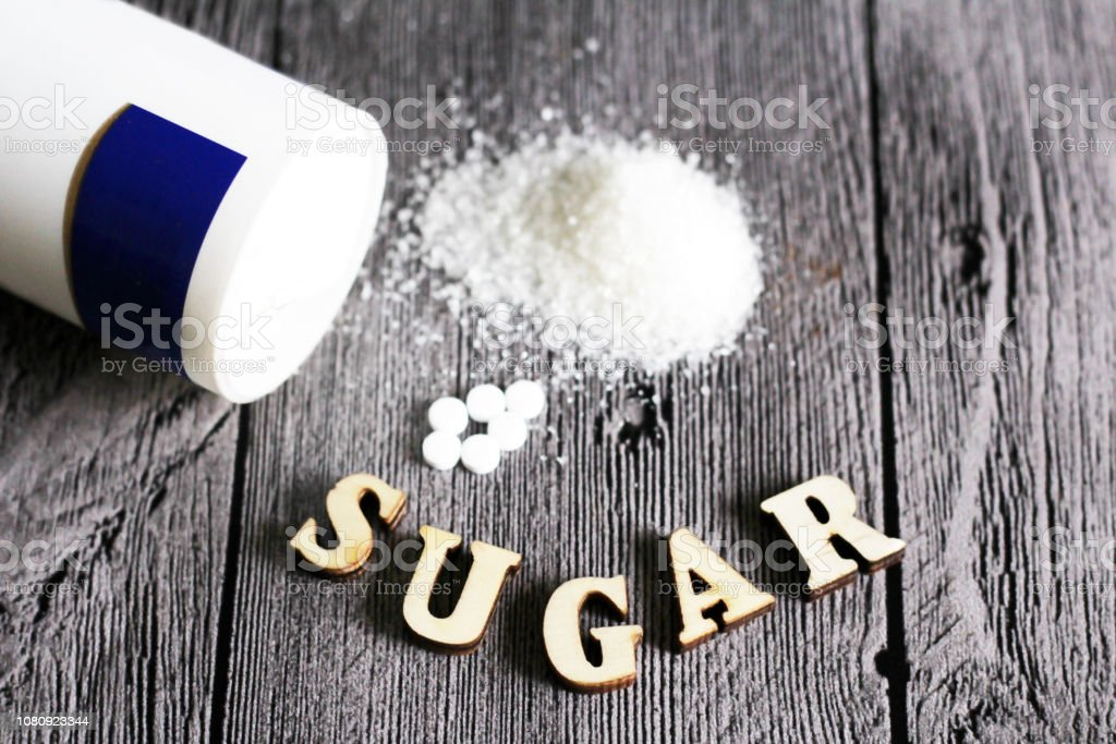 Sweetener tablet and sugar. Text sugar wooden letters. stock photo