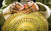 Charleston, South Carolina, USA -March 26, 2019-A craftsperson in the Charleston City Market creates a beautiful sweetgrass basket from locally grown grasses and bull rushes in much the same way people in the Charleston area have done for over 300 years.
