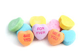 West Palm Beach, USA - January 23, 2012: This is a closeup studio shot of a pile of Sweethearts Candies. These candies are heart shaped pieces inscribed with romantic or flirtatious phrases. The visible phrases in this image are For Ever, Say Yes, and Me and You.  Sweethearts Candies are made by the New England Confectionary Company.
