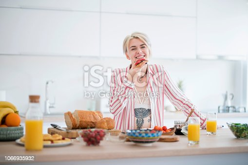 Young beauty preparing and eating breakfast in the kitchen
