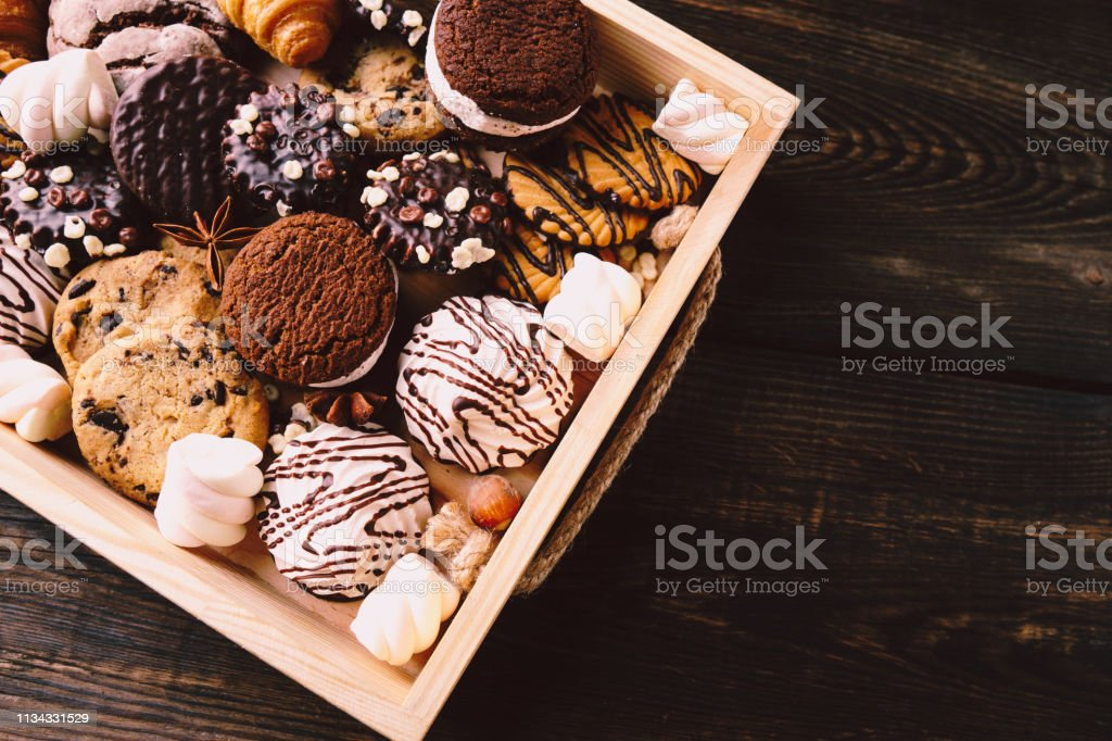 chocolate chip cookies, biscuits, sweets assortment in craft wooden...