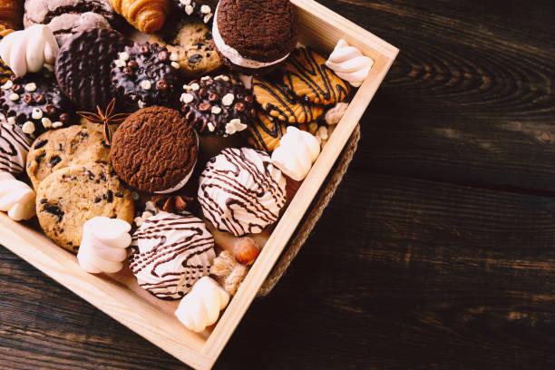 süßigkeiten-sortiment in handwerklicher holzkiste. süßes essen - low carb kekse stock-fotos und bilder