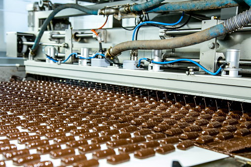 Sweets factory. Sweets production process. Conveyor belt with sweets on it.
