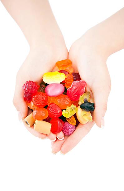 süßigkeiten mix in händen auf weißem hintergrund - haribo lakritz stock-fotos und bilder