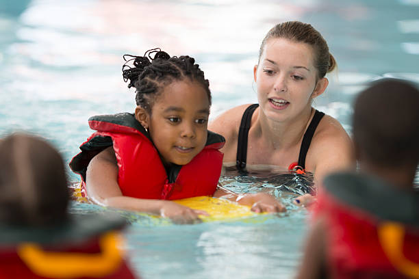 Swim Instructor Working with a Little Girl A multi-ethnic group of elementary age children are learning how to swim at the public pool. One little girl is holding onto a kick board and is swimming through the water. lifeguard stock pictures, royalty-free photos & images
