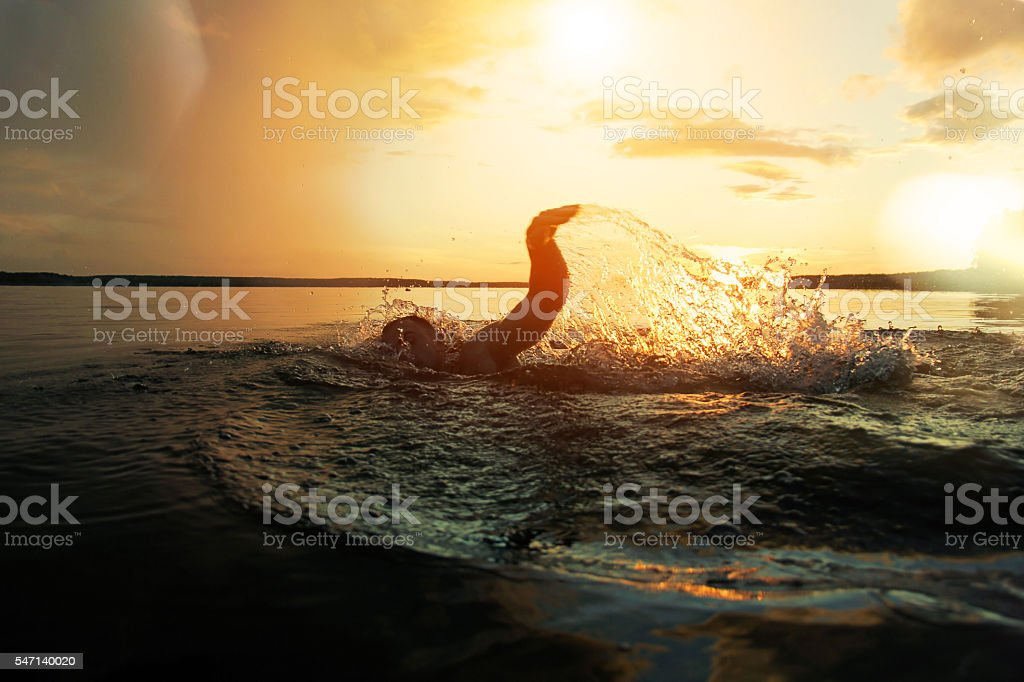 Swimmer conducts training in a lake at sunset stock photo