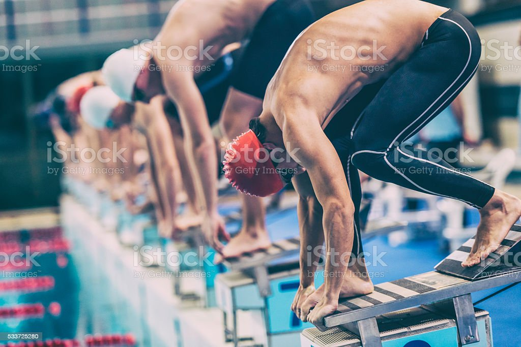 Swimmer crouching on starting block ready to jump stock photo
