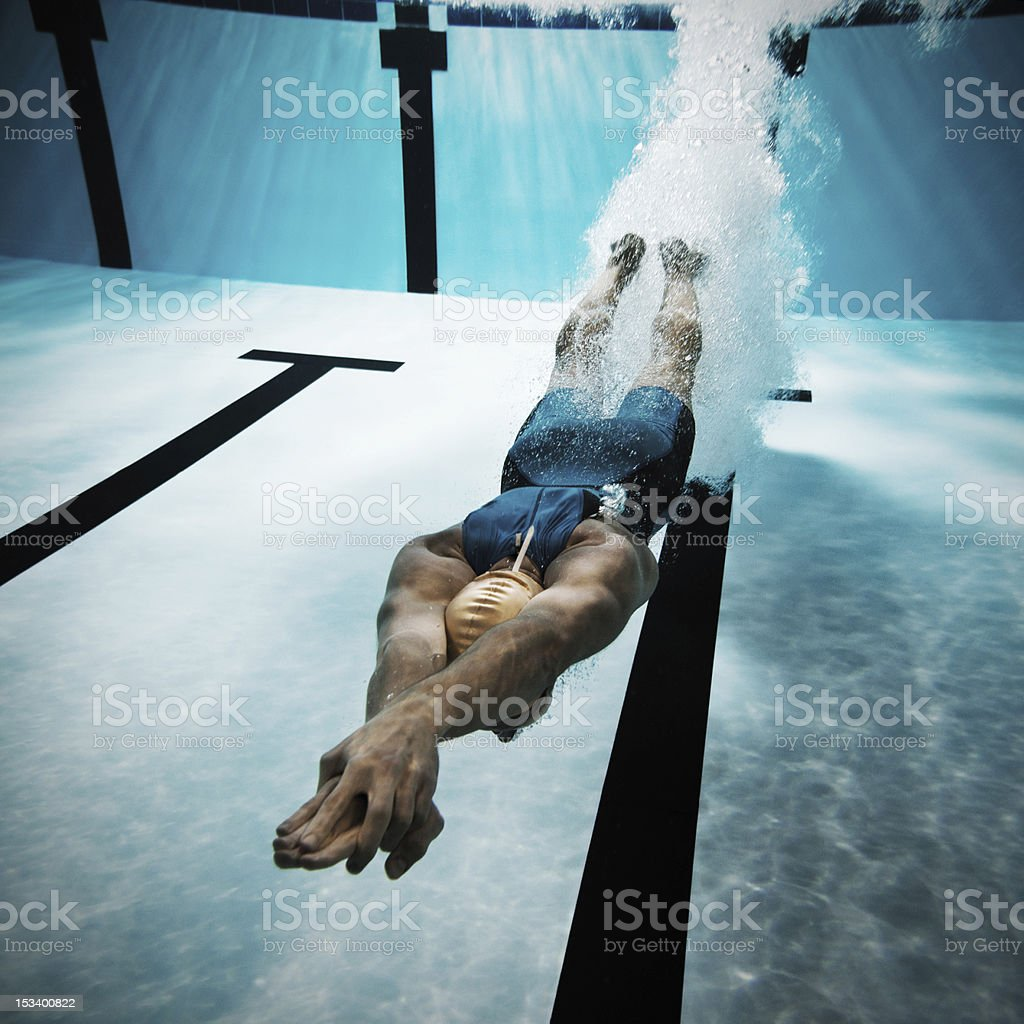 Swimmer diving after the jump in swimming pool stock photo
