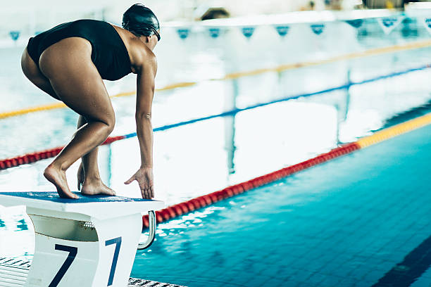 olympic swimming pool stock photo swimmer on starting block stock photo - Olympic Swimming Starting Blocks
