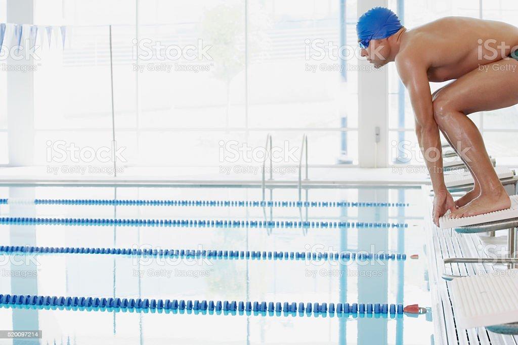 Swimmer on starting blocks stock photo