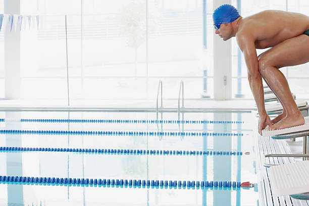 swimmer on starting blocks - starting block photos et images de collection