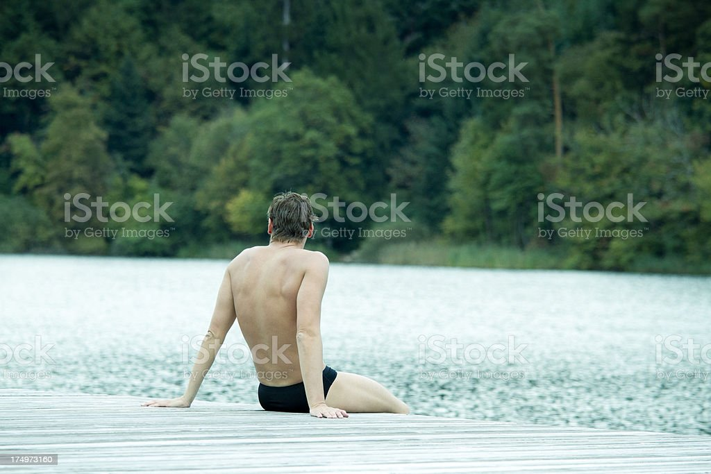 Swimmer sitting on jetty royalty-free stock photo