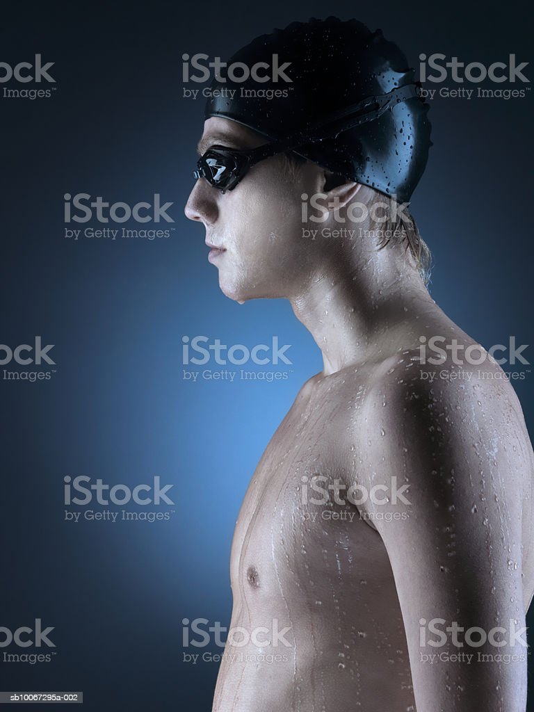 Swimmer standing against blue background, side view, close-up foto de stock libre de derechos