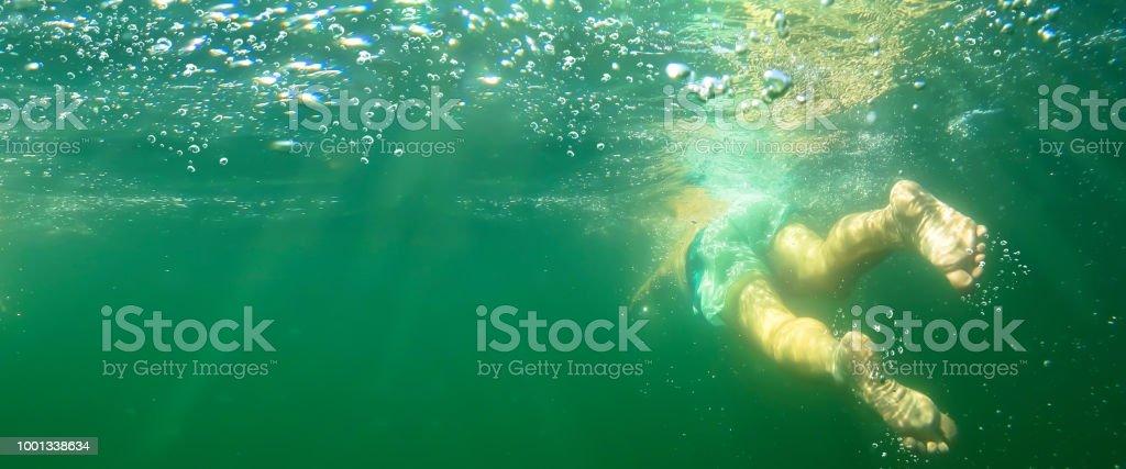 Schwimmer unter Wasser gegen Sonnenlicht – Foto