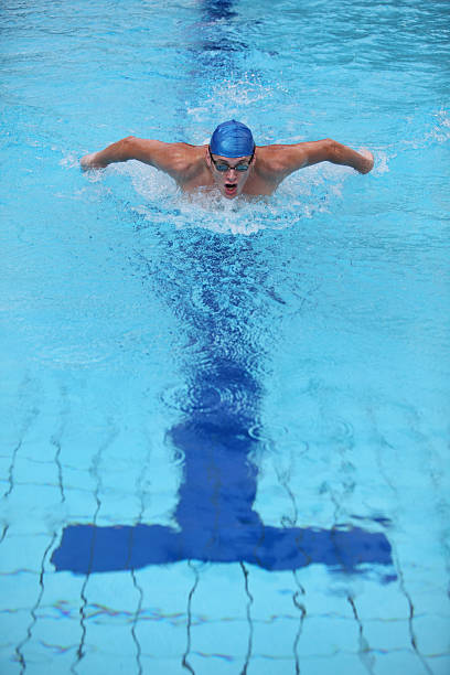 Swimmer with blue cap performing butterfly stroke in pool stock photo